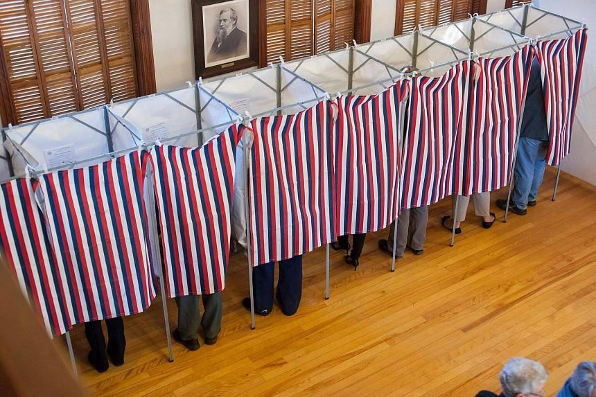 Voters cast their ballots at the Sutton town hall in the US presidential election on Nov 8, 2016, in Sutton, New Hampshire.