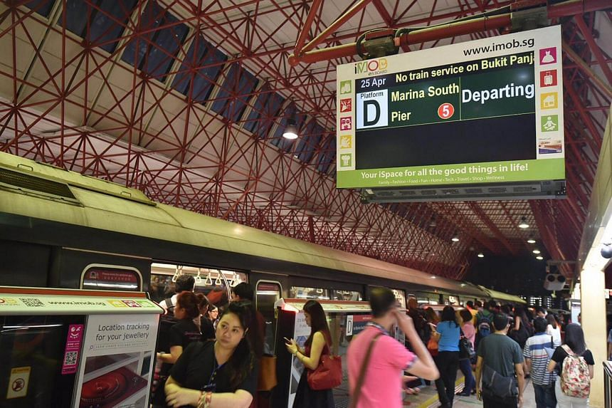 Commuters on the platform at Jurong East MRT station on April 25, 2016, The screen shows a notice about the disruption in train service.