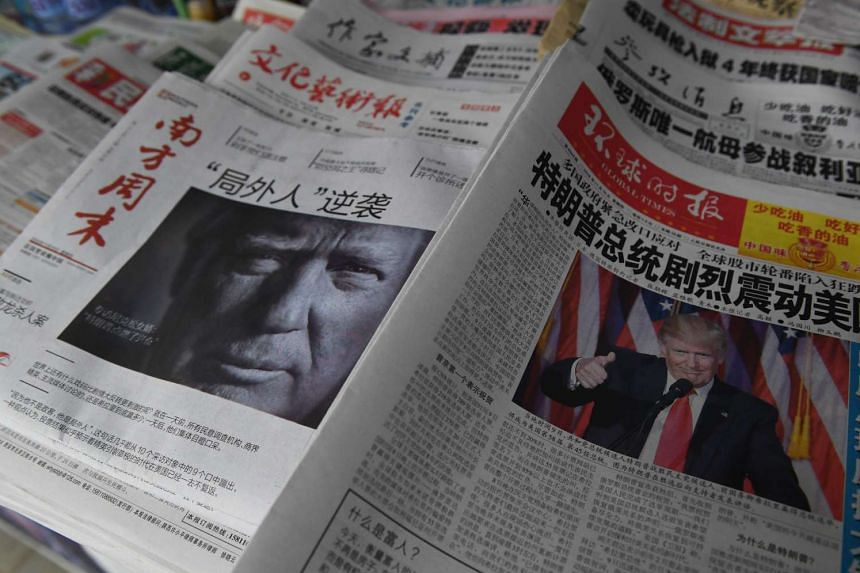 Chinese newspapers feature front page photos of US President-elect Donald Trump at a news stand in Beijing.