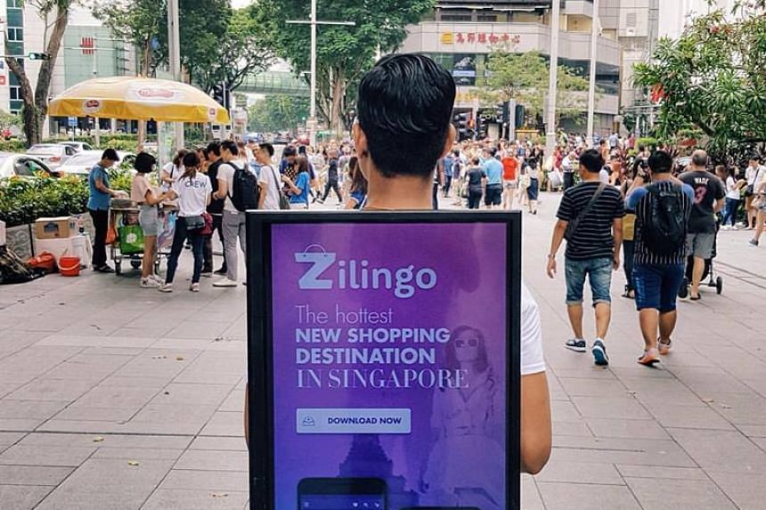 A man wearing a sign promoting the Zilingo app on Orchard Road, Singapore.