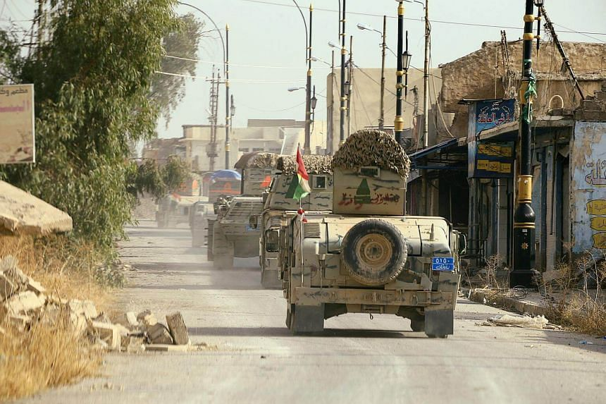 Peshmerga forces ride on military vehicles in the town of Bashiqa, after it was recaptured from the ISIS soldiers, east of Mosul, Iraq on Nov 9, 2016.