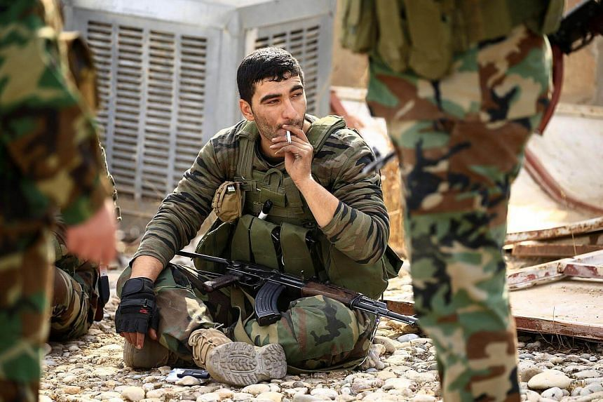A member of Peshmerga forces smokes in the town of Bashiqa, after it was recaptured from the ISIS soldiers, east of Mosul, Iraq on Nov 9, 2016.