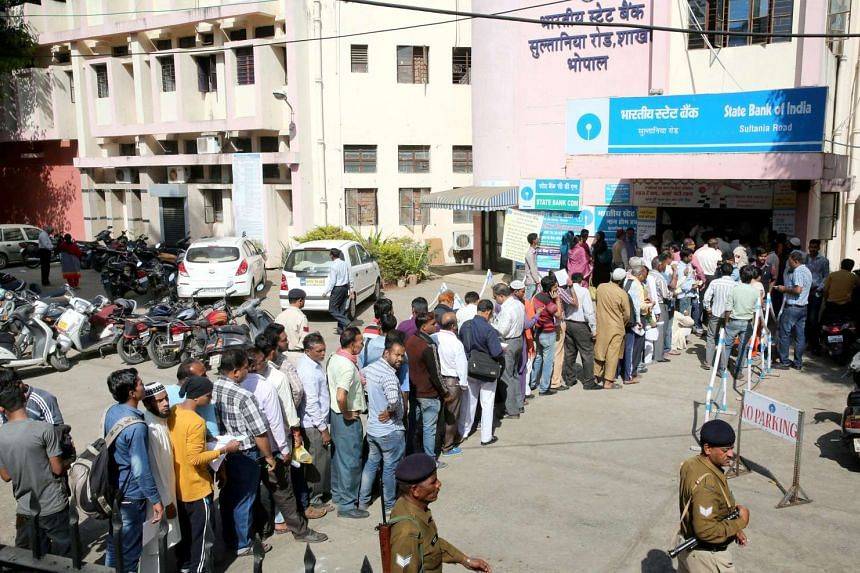 People stand in queue outside a bank to exchange discontinued Indian rupee notes for newly issued notes in Bhopal, India on Nov 10, 2016.