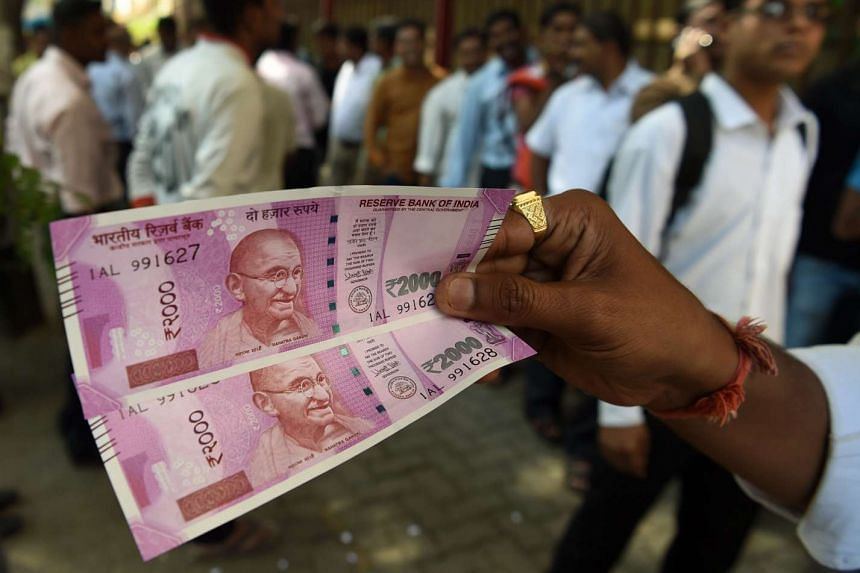 A man displays new 2000 rupee notes outside the Reserve Bank of India (RBI) in Mumbai on Nov 10, 2016.