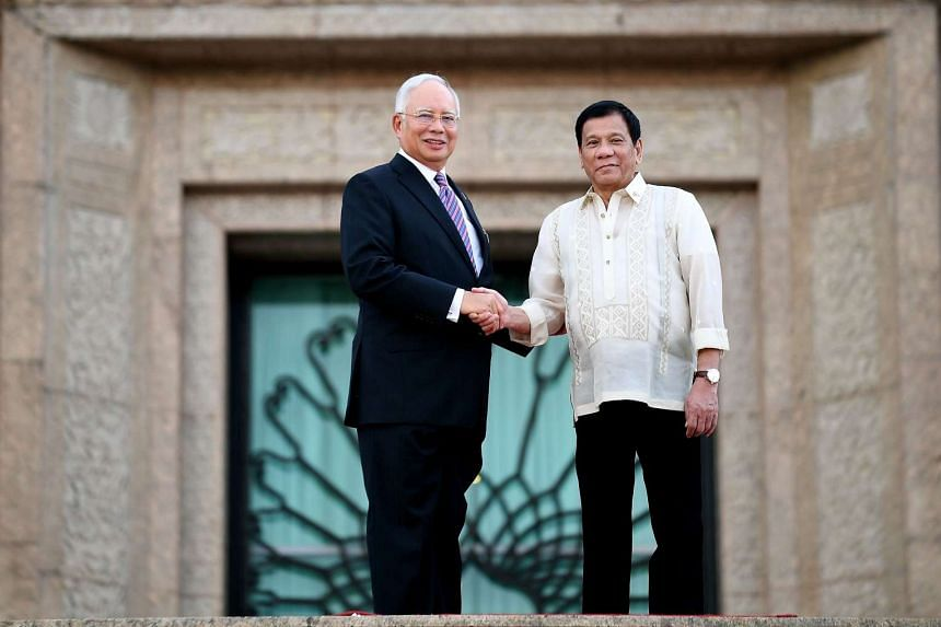Mr Duterte and Mr Najib shake hands before the welcoming ceremony.