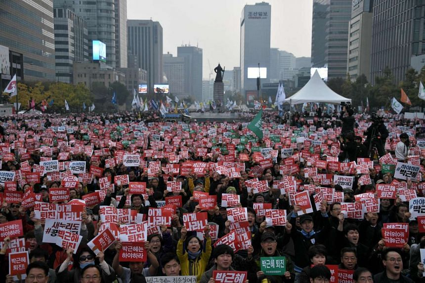 Demonstrators hold placards calling for the resignation of South Korean President Park Geun Hye in Gwanghwamun square in central Seoul on Nov 5, 2016.