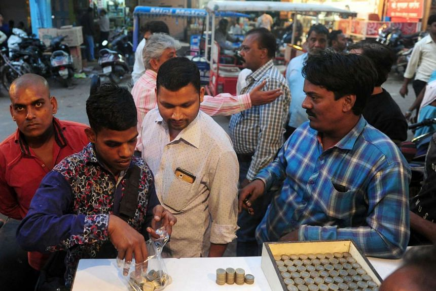 Indian residents exchange 500 rupee notes for coins at a roadside money changer, who charges 100 rupees per transaction, in Allahabad on Nov 9, 2016.