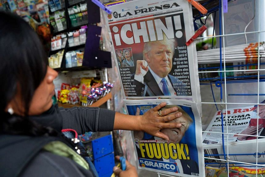 A newspaper vendor hangs on a rack newspapers with headlines about on the eventual triumph of Donald Trump on Nov 9, 2016 in Mexico City.