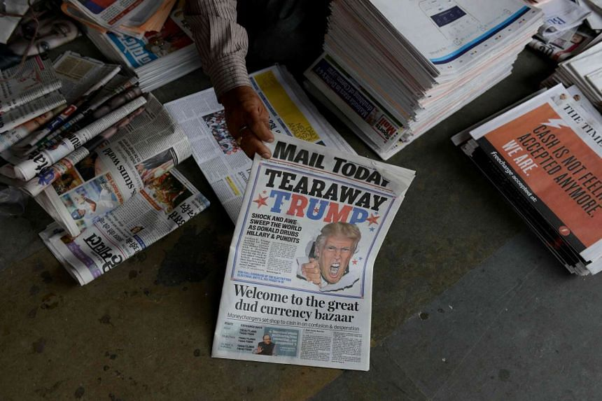 An Indian Newspaper vendor arranging newspapers featuring Donald Trump's victory in the US presidential elections on their front pages, in New Delhi, on Nov 10, 2016.