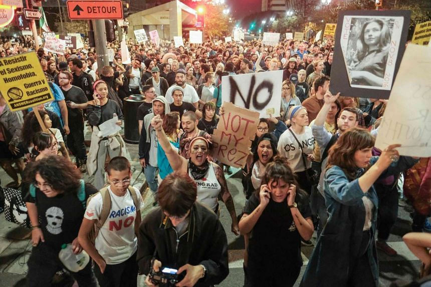 Demonstrators gather to protest a day after president-elect Donald Trump's victory, at a rally outside Los Angeles City Hall in Los Angeles, California, on Nov 9, 2016.