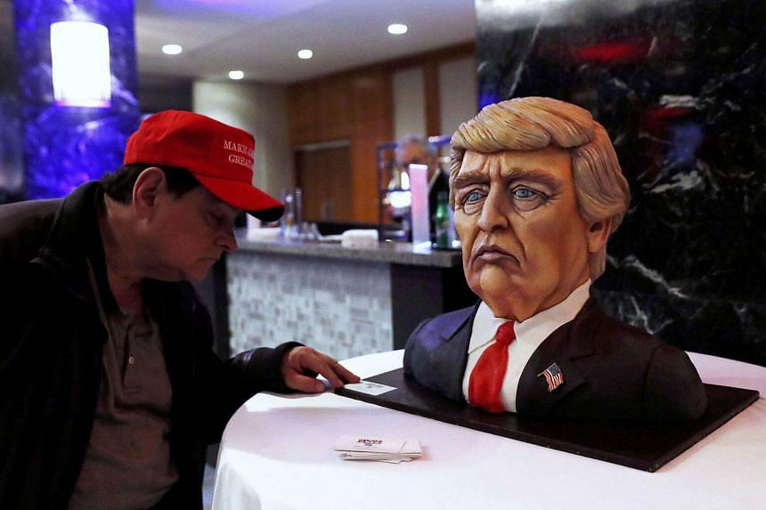A man checking out a Trump cake ahead of the rally in New York City, New York, US, on Nov 8, 2016.