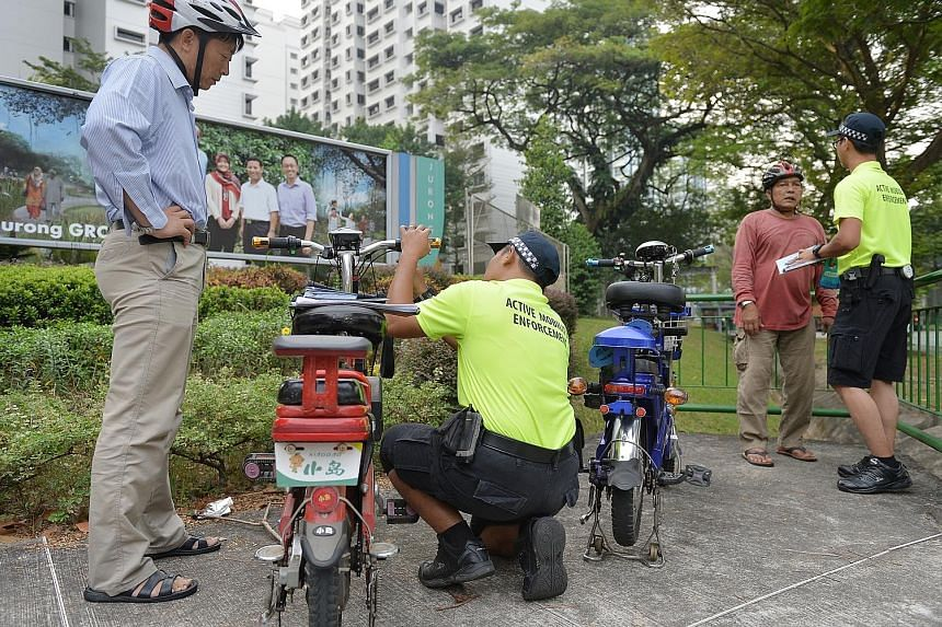 Active Mobility Enforcement Officers from the Land Transport Authority inspecting motorised bicycles. The Bill seeks to provide the Land Transport Authority with powers to enforce the new rules, such as examining whether the personal mobility devices