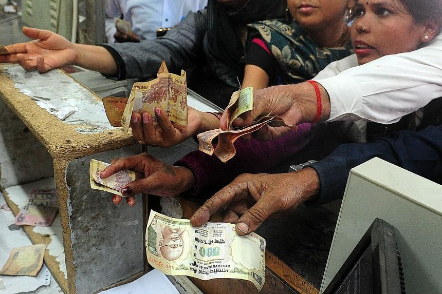 Passengers using 500-rupee and 1,000-rupee notes to buy train tickets in Allahabad yesterday. The move to scrap the banknotes is part of a crackdown on corruption.