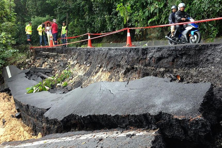The floods in Penang have forced residents in the capital, George Town, to get around by boat (above) and caused a road at Batu Ferringhi to collapse (below). The federal and state governments blame each other for not preventing the flooding.