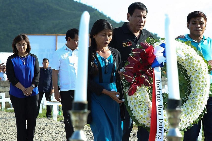 "Mr Duterte (in black top) and Mrs Robredo (far left) in Tacloban City to mark the third anniversary of the Haiyan disaster. The President said he mentioned ogling the Vice-President's legs ""to make people laugh because I was angry"". The super typhoon"