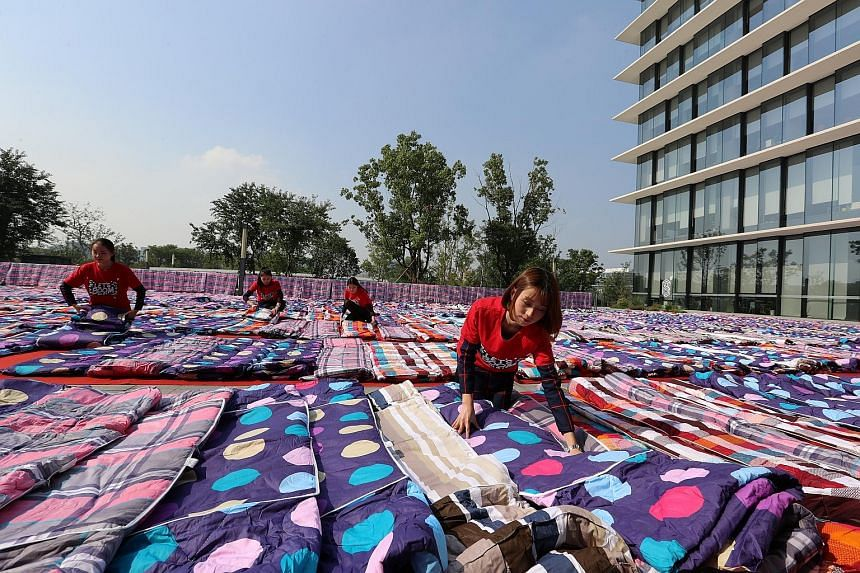 """Alibaba's employees in China's Zhejiang province drying quilts for their company staff to use as they rest, in preparation for tomorrow's Singles' Day global shopping festival. Sales on Nov 11 - the """"double elevens"""" - are supposedly watched as a baro"""