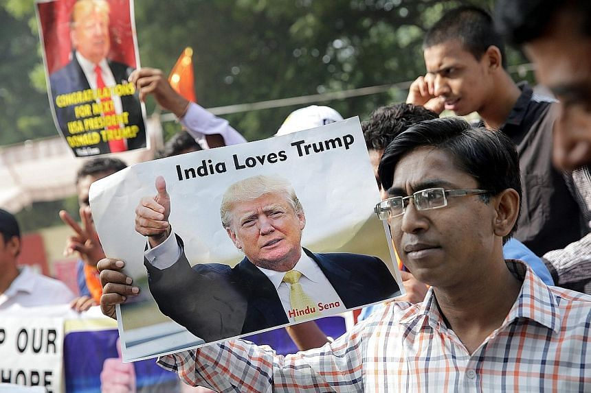 Far left: Activists from India's right-wing Hindu Sena in New Delhi yesterday celebrating Mr Trump's win. Left: A passer-by in Tokyo yesterday picking up the latest news on the US election.