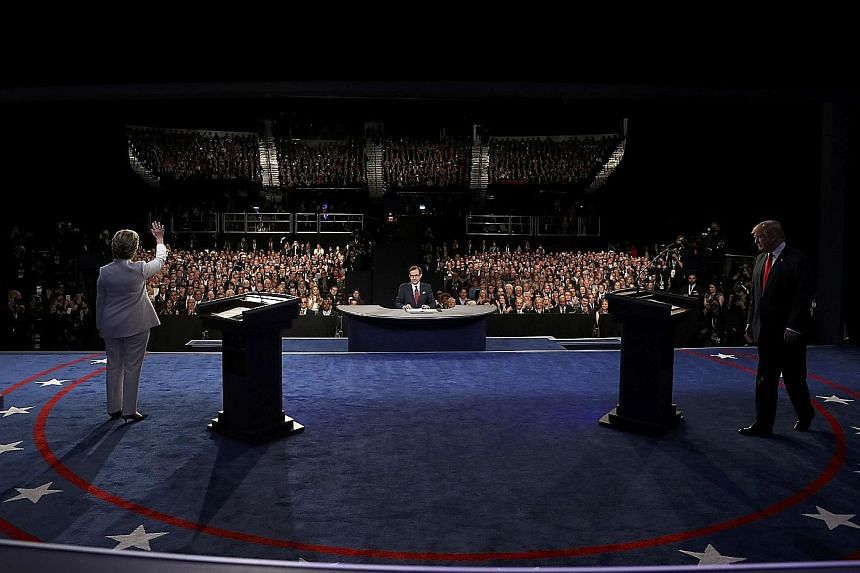 Mrs Clinton and Mr Trump at the third US presidential debate last month. Despite Mrs Clinton sitting atop the polls after impressive debate performances, having a significantly larger war chest and a grassroots operation that dwarfed her opponent's,