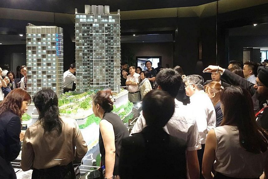 Interested viewers of residential project Cairnhill Nine (above). Sales at this and other residential developments including The Nassim (left) helped to boost CapitaLand's third-quarter profit to $247.5 million from $192.7 million a year earlier. Chi