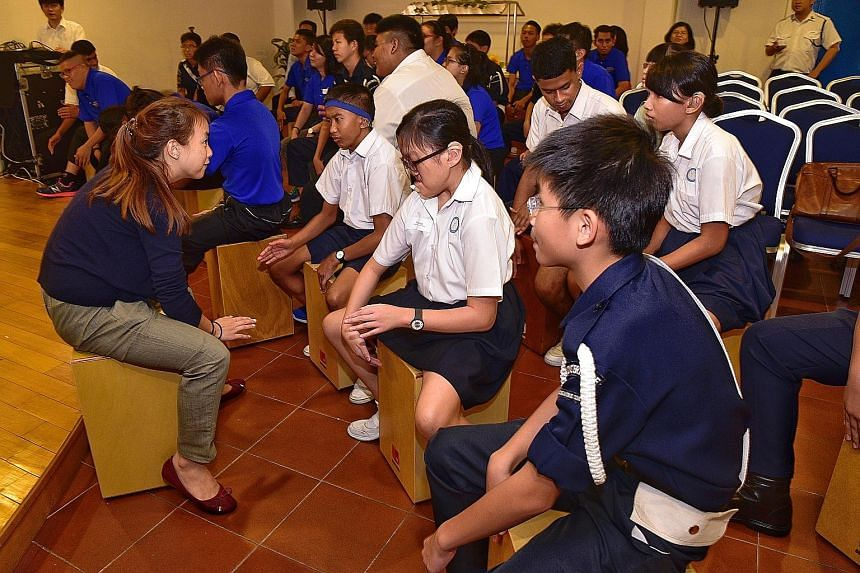 Above left: Ms Janis Wong, a teacher at the Singapore School for the Deaf, helping students during a cajon drumming workshop conducted by social enterprise Beat'abox at the Boys' Brigade Share-a-Gift media conference. Above right: Joyce Ong and Raja