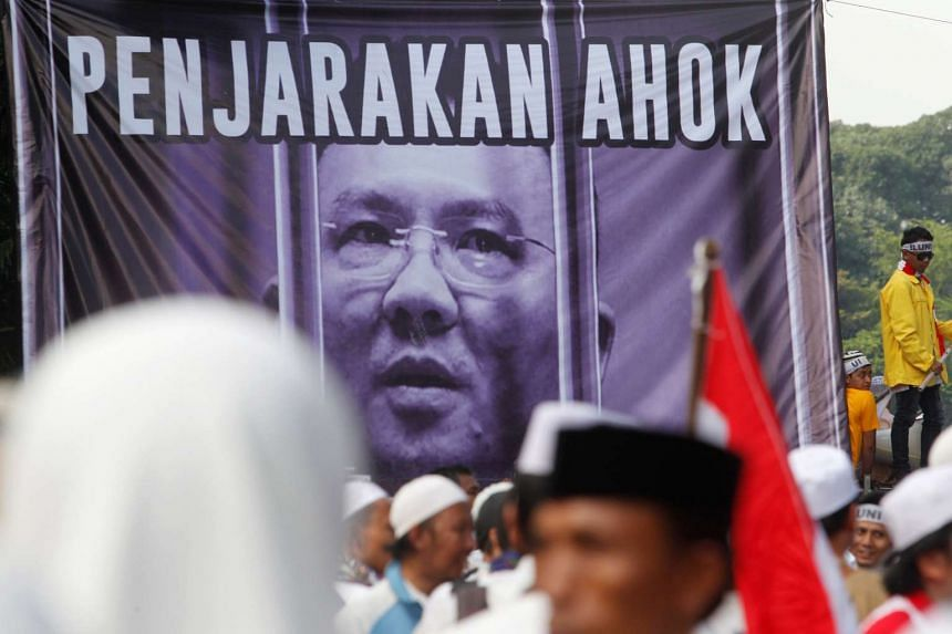 """Members of hardline Muslim groups stand around a poster that reads """"Ahok should be jailed"""" during protest in Jakarta on Nov 4, 2016."""