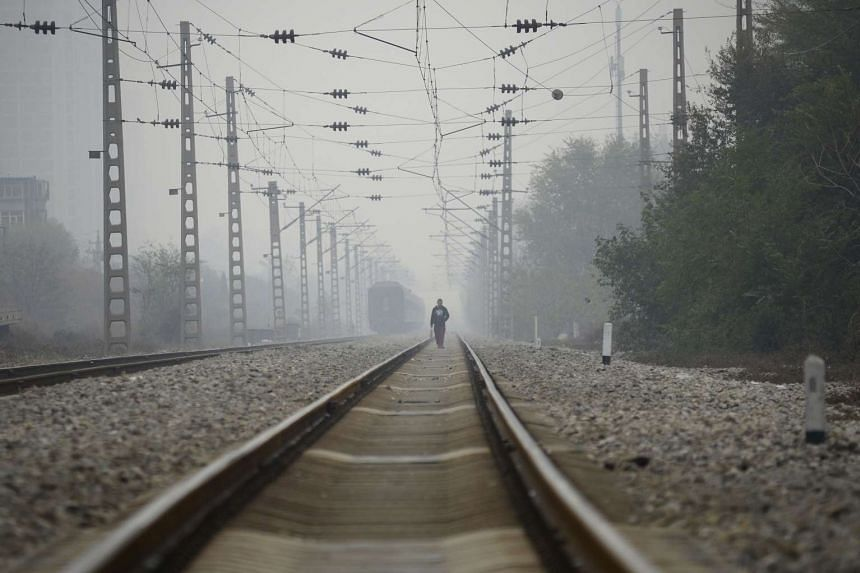 A man walks along a train track in Beijing on November 10, 2016.