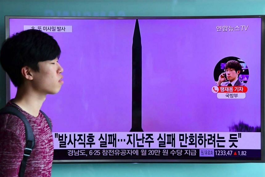 A man walks past a television screen showing file footage of North Korea's missile launch at a railway station in Seoul.