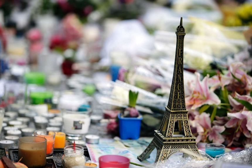 """A November 2015 file photo shows a miniature Eiffel tower, candles and flowers displayed at a makeshift memorial outside """"Le Carillon cafe"""" in Paris."""