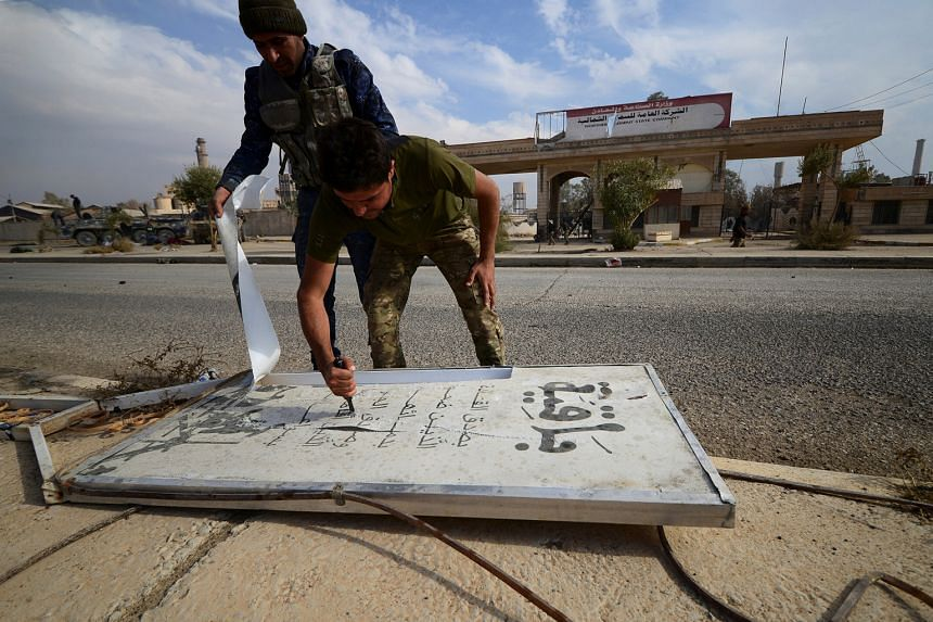 Members of an Iraqi special forces police unit tearing up a signboard of the Islamic State in Iraq and Syria south of Mosul on Tuesday, after government forces captured the area in the ongoing 