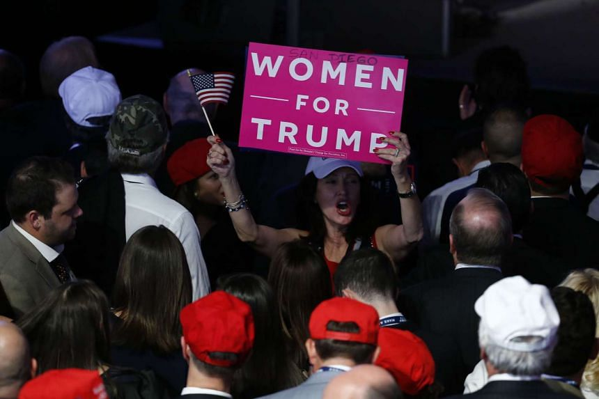 """An attendee holds a """"Women For Trump"""" sign during an election night party for US President-elect Donald Trump at the Hilton Midtown hotel in New York."""