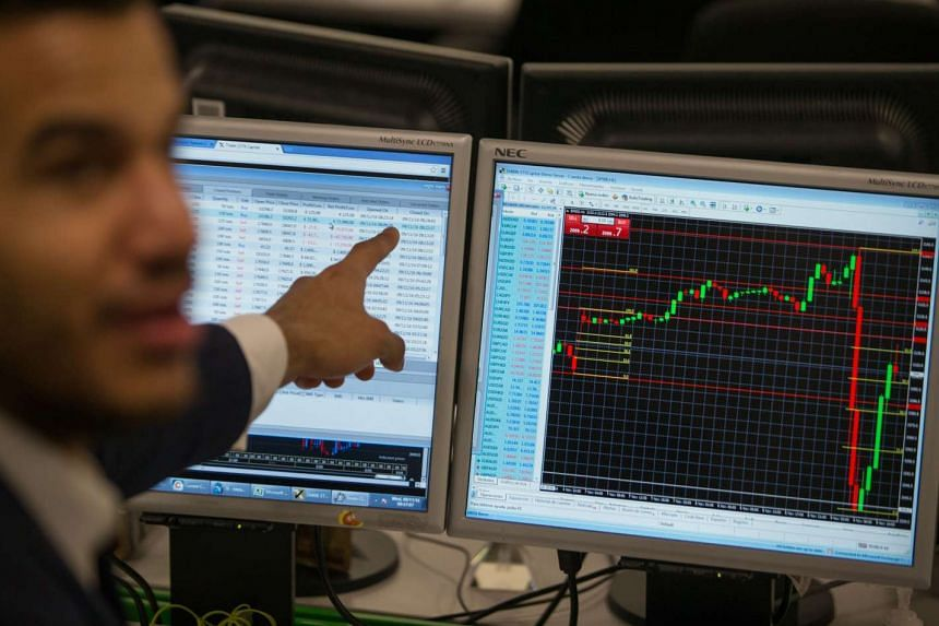 A trader at ETX Capital in London points to a trading terminal screen showing the S&P 500 Index on Nov 9, 2016.