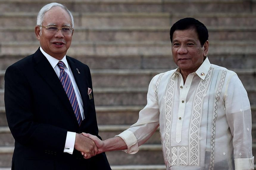 Malaysia's Prime Minister Najib Razak shakes hands with Philippine President Rodrigo Duterte during a welcoming ceremony at the prime minister's office in Putrajaya on Nov 10, 2016.