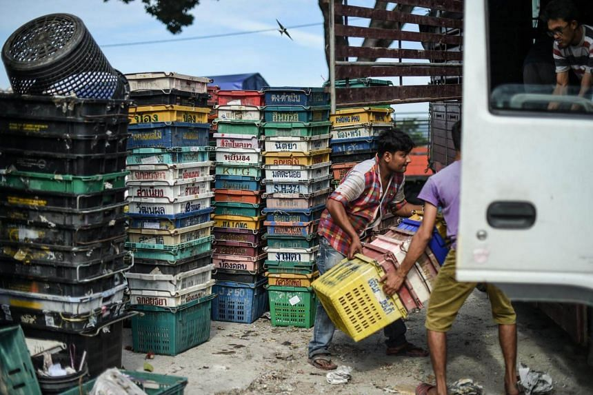 Workers carrying empty fruits boxes into a lorry at a wholesale market in Kuala Lumpur on Sept 23, 2016.