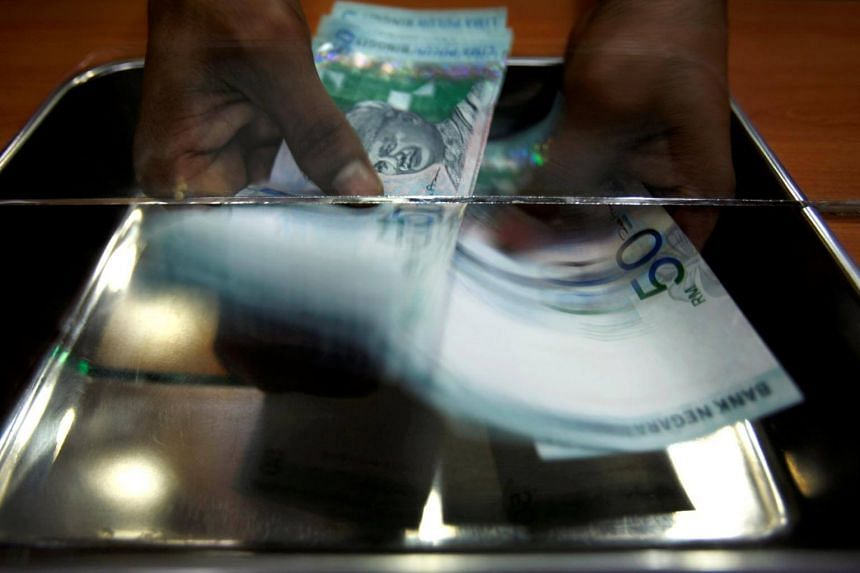 A money changer counting ringgit at a shop in Putrajaya, outside Kuala Lumpur.