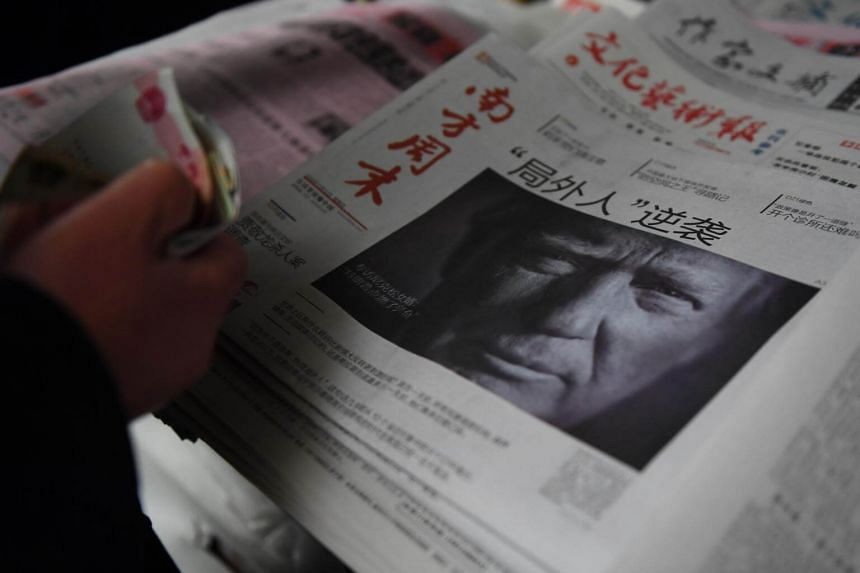 A man buys a Chinese newspaper featuring Donald Trump on the front page in Beijing on Nov 10, 2016.