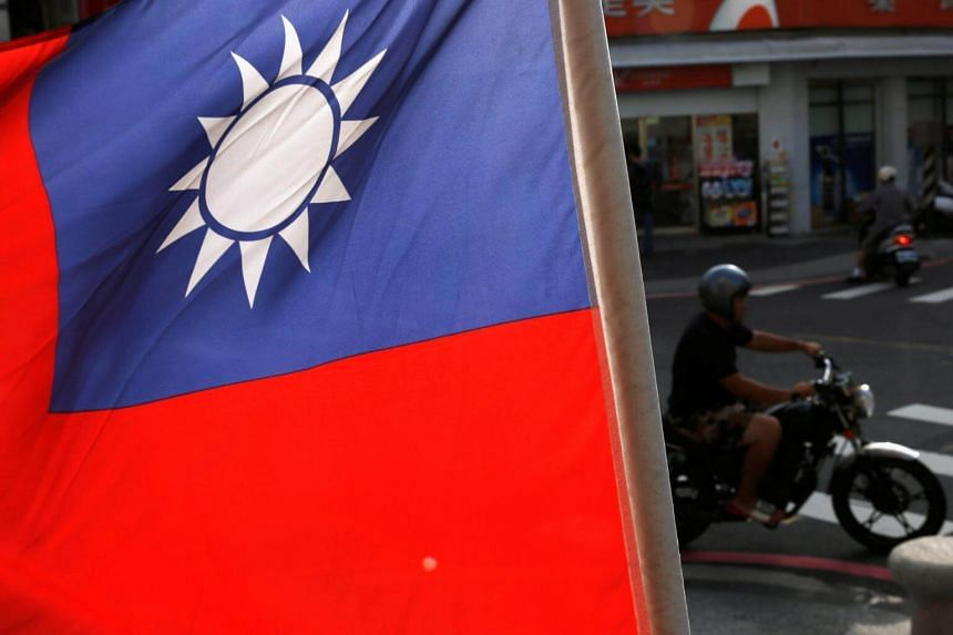 Motorcyclists ride past a Taiwanese national flag.