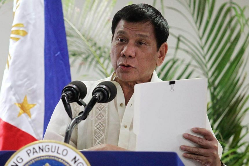 Philippine President Rodrigo Duterte holding a copy of his speech as he speaks after arriving from Malaysia, at Davao International airport, on Nov 11, 2016.