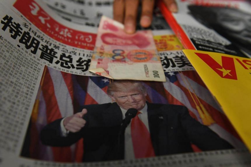 A vendor picking up a 100 yuan note above a newspaper featuring a photo of US president-elect Donald Trump, at a news-stand in Beijing on Nov 10, 2016.