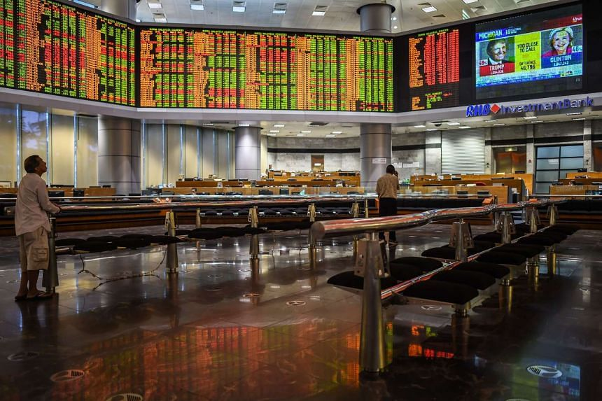 Traders monitor electronic boards showing stock movements during the final day of the US presidential election at a private stock exchange in Kuala Lumpur on Nov 9, 2016.