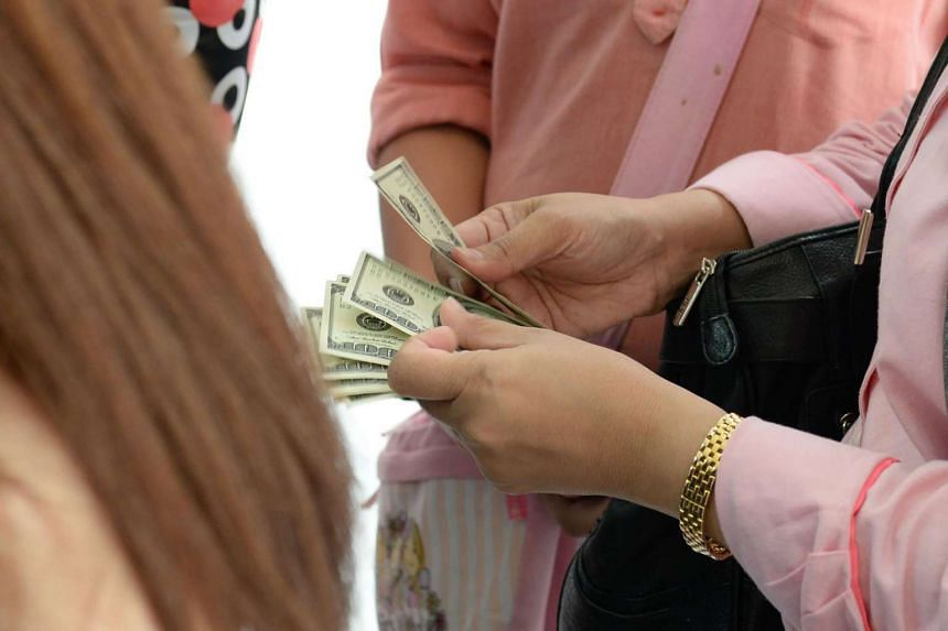 A woman counts her US dollars while queueing in front of a money changer at the Raffles Place business district in Singapore on Nov 9, 2016.