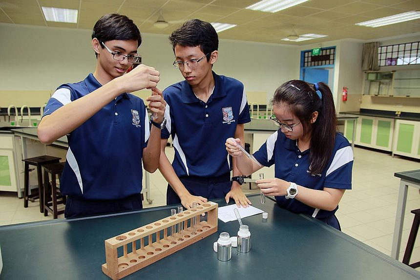 Queenstown Secondary students (from left) Zephaniah Lim, Koung Zin and Zoe Tan demonstrating how they mixed essential oils with ethanol and glycerin to create scents.