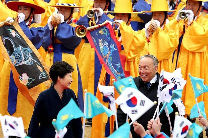 Ms Park and Kazakh President Nursultan Nazarbayev being greeted by children during a welcome ceremony in Seoul yesterday. Mr Nazarbayev is in South Korea to boost ties between the two countries, but the current political scandal is casting dark shado