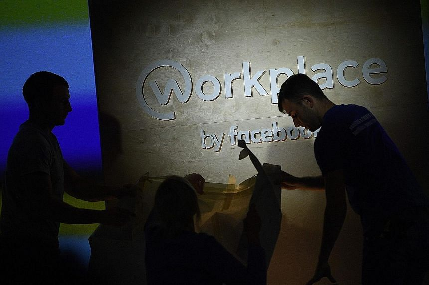 People preparing the stage ahead of an event to launch Workplace, Facebook's chat platform for businesses, in London on Oct 10. Workplace will replace the Public Service Division's in-house development called Cube. The decision to go with Workplace w