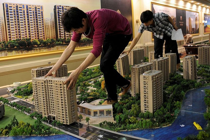 Employees setting up model flats for an exhibition in Hangzhou. The city has implemented new rules for home buyers, including higher down payments for second homes and curbs on non-residents buying properties.