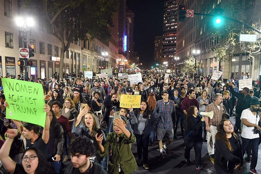 Demonstrators marching in an anti-Trump protest in Oakland, California, on Wednesday. Protesters marched in college campuses, blocked roads and surrounded Trump properties in at least 25 cities nationwide as they rallied against Mr Trump's victory in