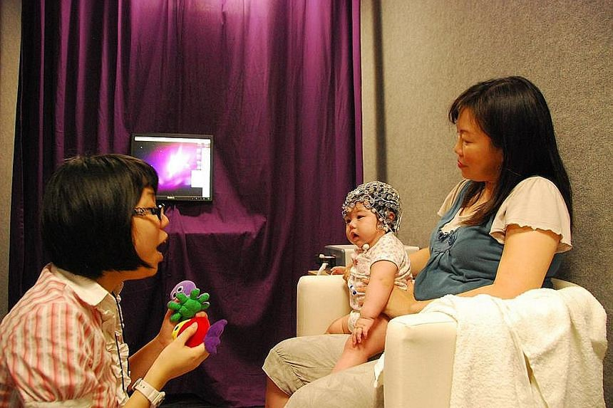 "A baby wears sensors that track brain activity in a study that tested the difference in how babies reacted to ""standard"" and ""oddball"" sound stimuli. The research, done by Dr Anne Rifkin-Graboi and Dr Cai Shirong (left), found that those babies whose"