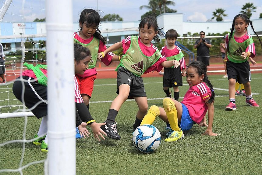 Primary school pupils playing a football match at the Fifa Girls Football Festival yesterday at Serangoon Stadium. The third edition of the event attracted about 450 girls from 39 teams, who competed in three categories - Under-8, U-10 and U-12. Whil