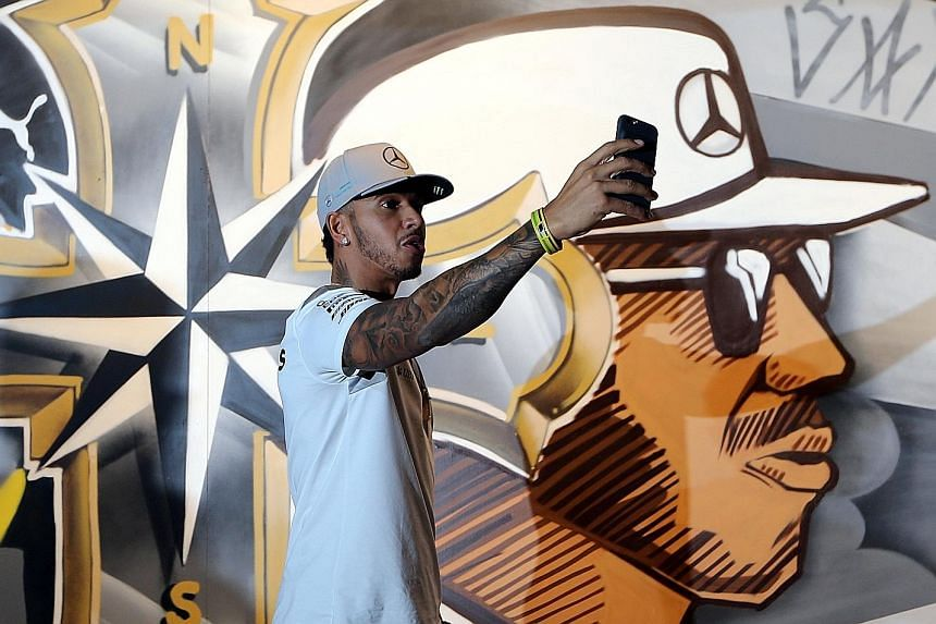 "Mercedes driver Lewis Hamilton taking a selfie in front of graffiti art during a promotional event in Sao Paulo. The two-time defending champion admits that there is more of a chance he will lose the F1 title than win it and that is ""hard to swallow"""