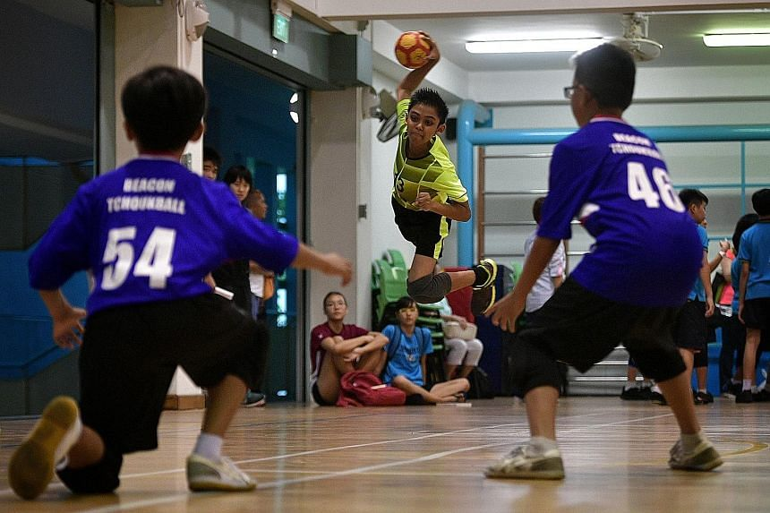 Above: Edric Soong holds the championship trophy. Right: Farrer Park Primary's right winger Ashif Rahman, 11, tries to shoot at the frame against Beacon Primary during the final of the SPH Foundation National Primary Schools Tchoukball Championship.