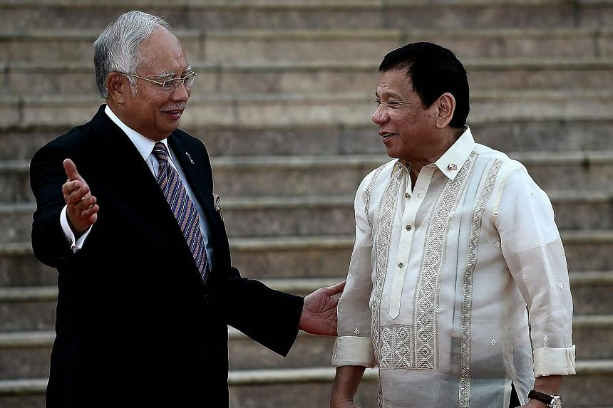 """Malaysia's PM Najib (left) welcoming visiting Philippine President Duterte in Putrajaya yesterday. Mr Najib told reporters that on the issue of Sabah, the Philippines' claim """"will not be addressed immediately""""."""